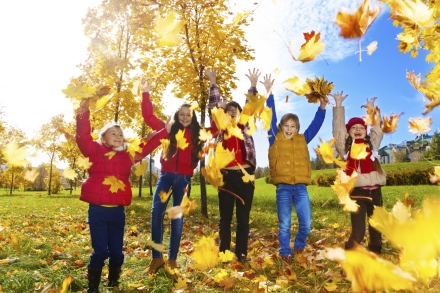 Group of kids throw autumn leaves